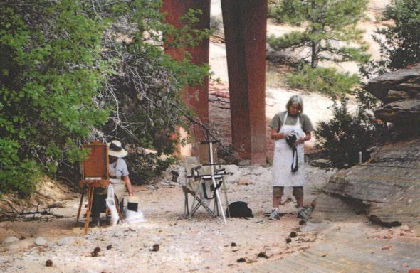 "Dixon Retreat #2, May 2009. Now it is WAY warm! Location, location, location...the Dixon site was only 45 minutes from Zion National Park. At one time we had a goal to stop and paint at every car ""turn out"" on the road through the park. We hit quite a few. This is Barb and Rox painting in a wash, waiting for a flash flood to cool us off...lol."